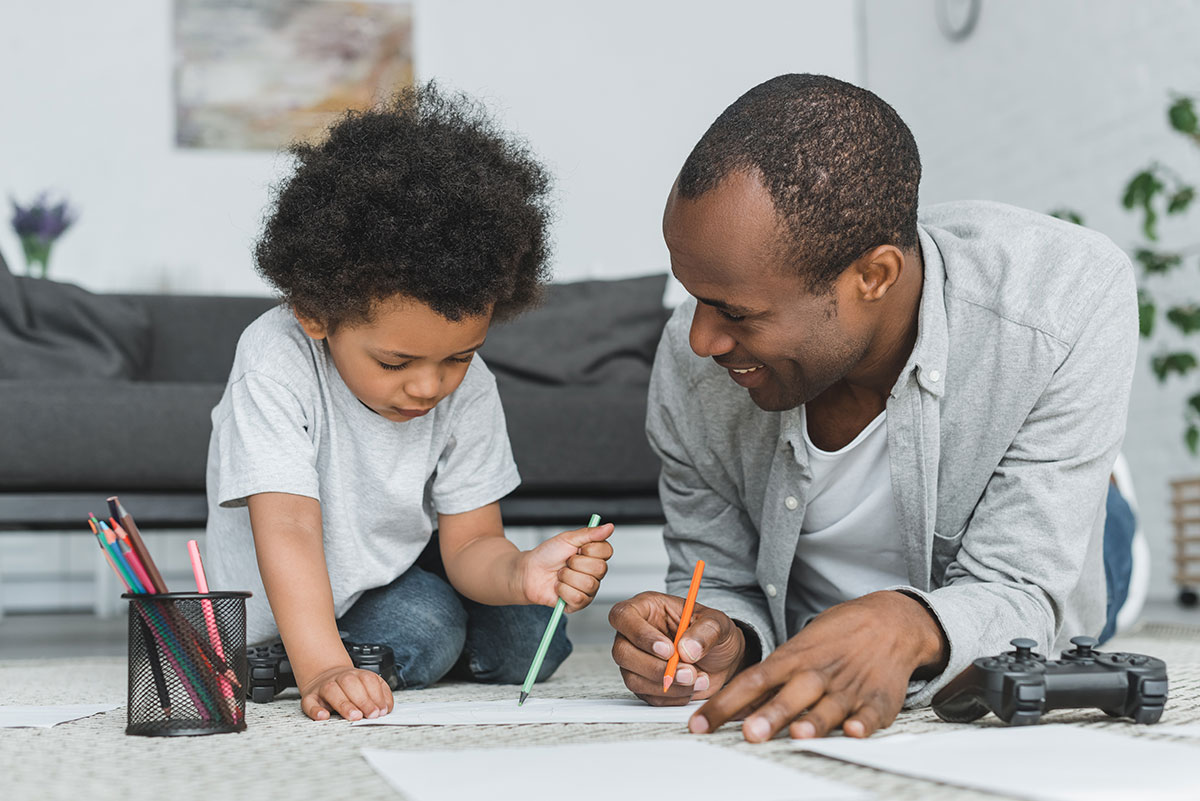Father and son drawing on the floor